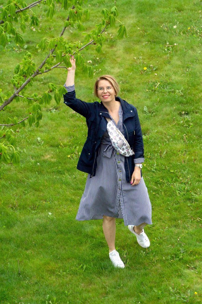 kobieta ubrana w koszulową sukienkę w paski
