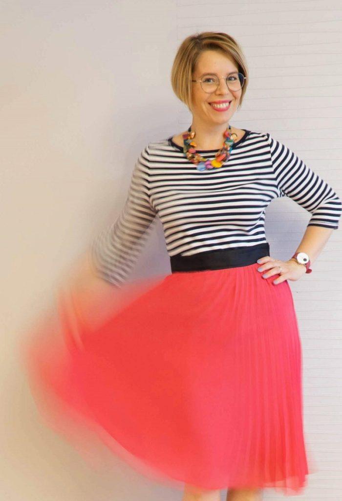 kobieta w pasiastej bluzce i plisowanej spódnicy
