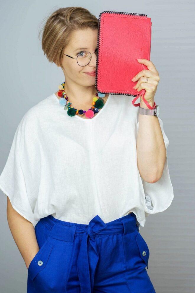 kobieta w białej bluzce i szafirowych szortach zasłaniająca twarz różową kopertówką