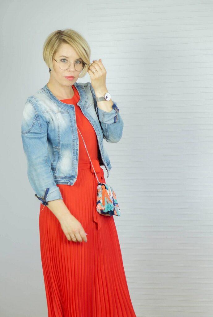 kobieta w czewronej plisowanej sukience i kurtce dżinsowej