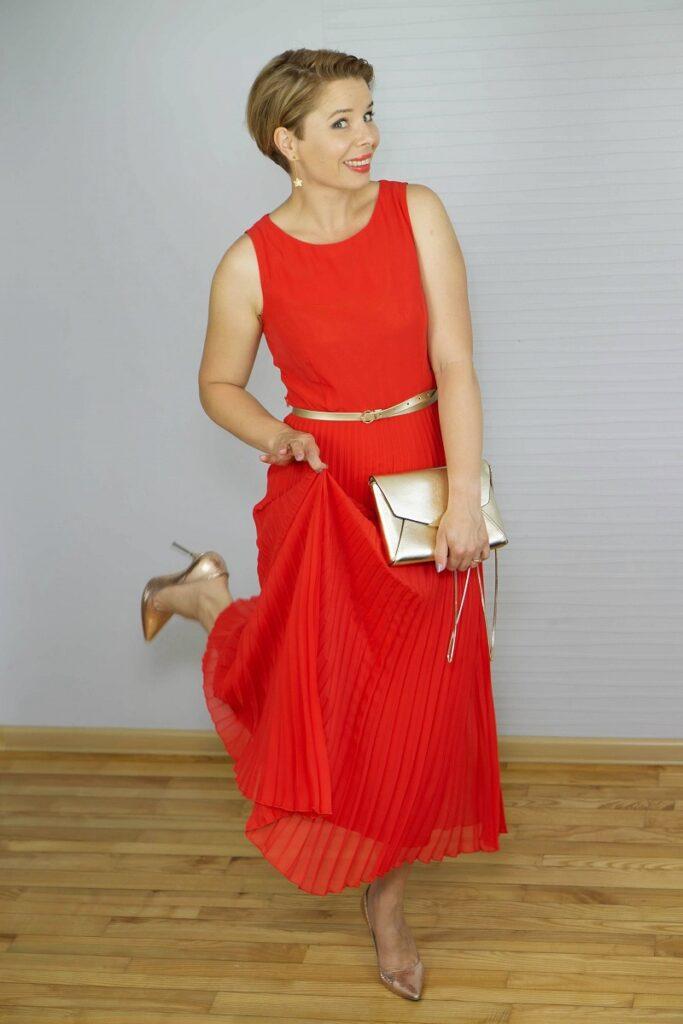 kobieta w długiej czerwonej plisowanej sukience