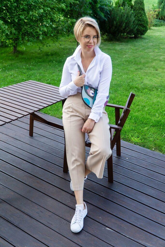 kobieta w białej koszuli i beżowych spodniach