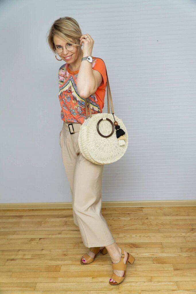 kobieta w pomarańczowej bluzce we wzory i beżowych spodniach