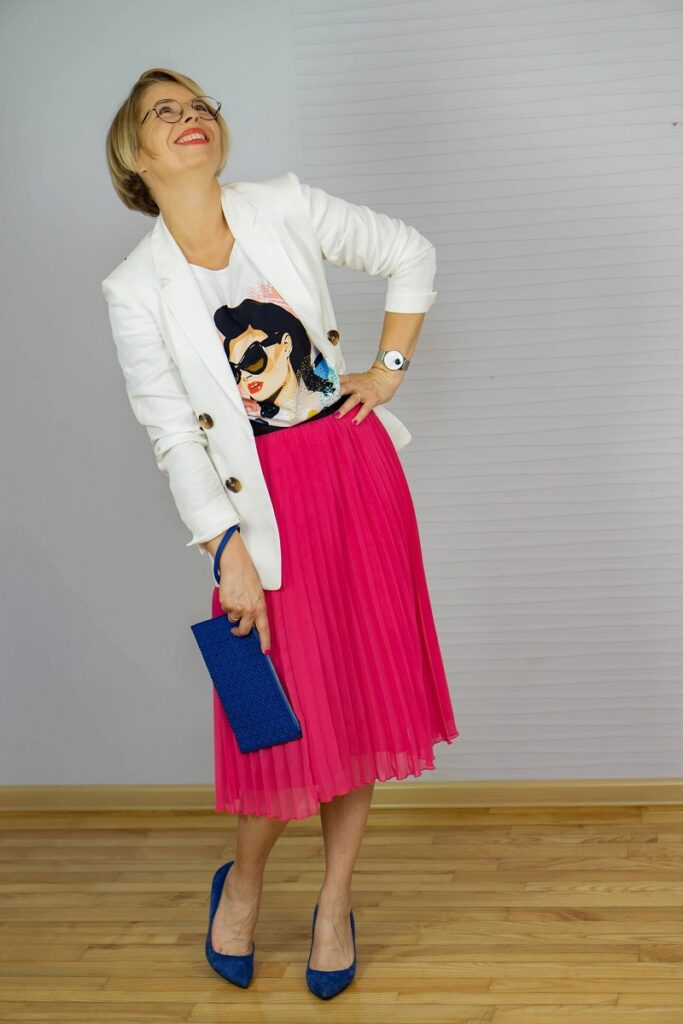 Kobieta w białej marynarce i różowej spódnicy