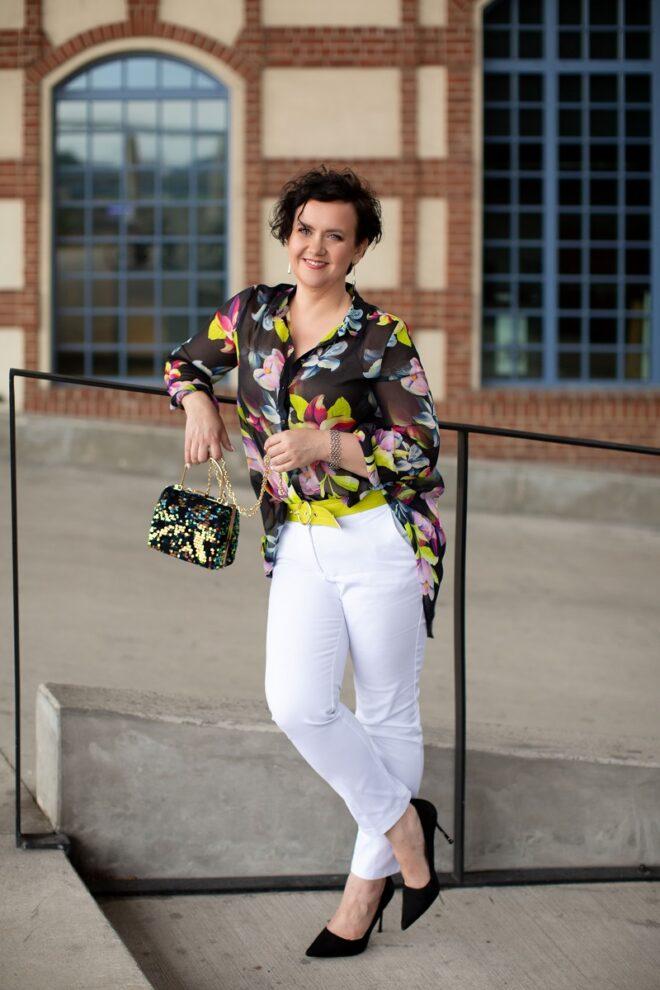 Kobieta w kolorowej bluzce i białych spodniach