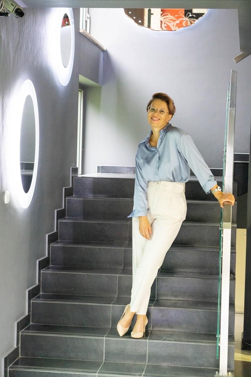 Stylizacje do pracy: błękitna koszula i kremowe spodnie prezentowane na modelce