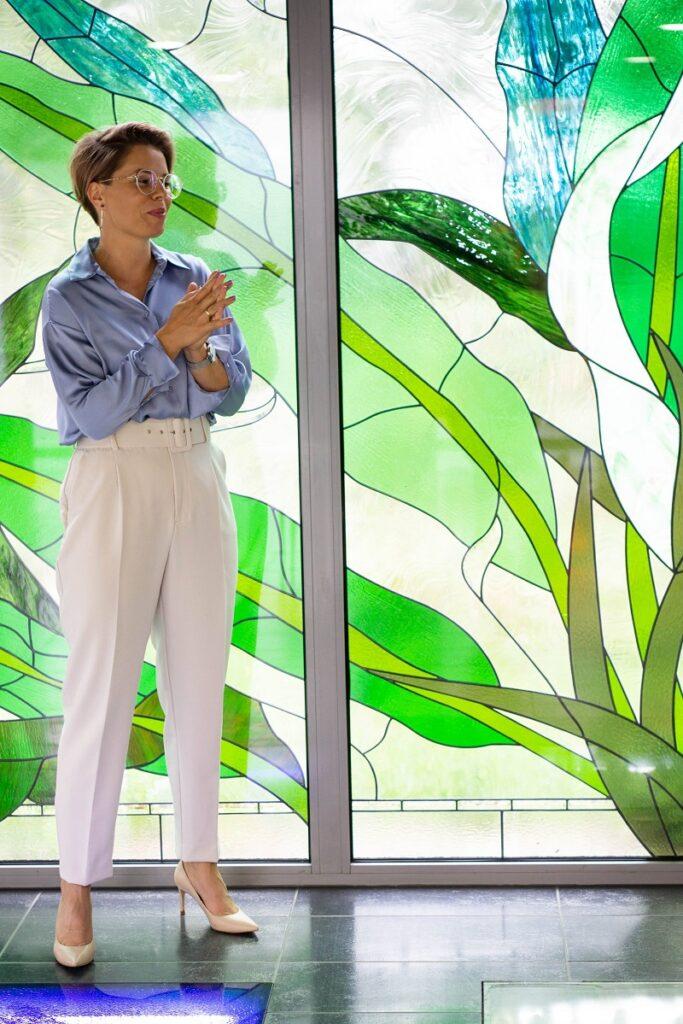 Błękitna koszula i kremowe spodnie prezentowane na modelce