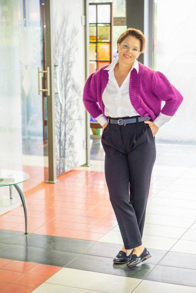 Stylizacje do pracy: biała koszula, fuksjowy sweter i granatowe spodnie prezentowane na modelce