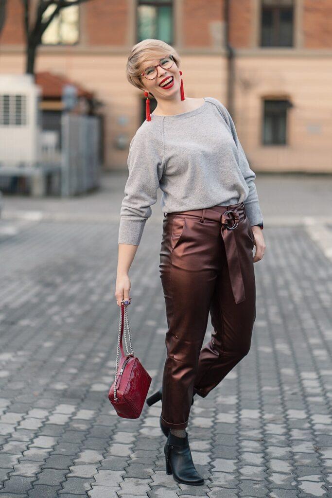 spodnie na duże uda: kobieta w szarym swetrze i spodniach z metalizowanej skóry