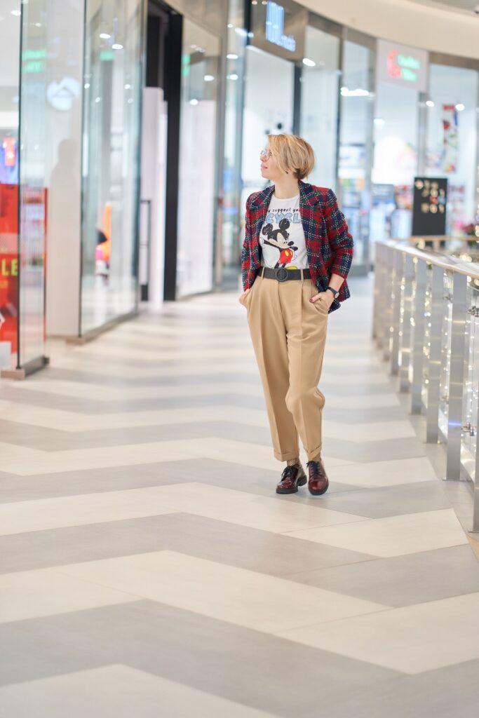 spodnie na duże uda: kobieta w szerokich beżowych spodniach i kraciastej marynarce ogląda wystawy w galerii handlowej