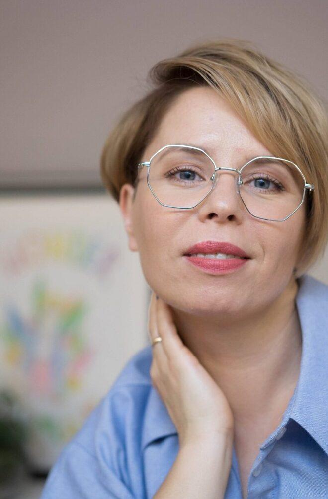 portret kobiety o krókich włosach w srebrnych okularach