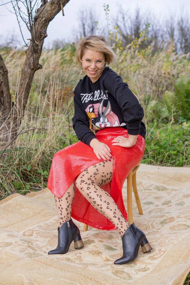 rajstopy - jak je nosić kobieta w czerownej cekinowej spódnicy i czarnej bluzie siedzi na krześle ustawionym w ogrodzie