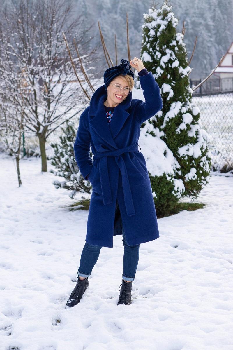 Kobieta w granatowym płaszczu i czapce pozuje na śniegu
